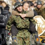 A soldier carries an elderly woman on his back as people are evacuated to a shelter at Kesennuma city in Miyagi prefecture