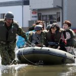 A soldier pulls a rubber boat carrying evacuated people at Ishinomaki city in Miyagi prefecture