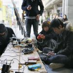 People charging up their mobile phones at a shopping street providing a free charging service at Sendai