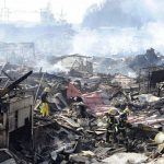 Search and rescue operation amidst smoldering debris in Kesennuma, northern Japan