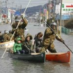 Hard at work - Japan Defense Force personel help people go through the flooded area by boats in Ishinomaki