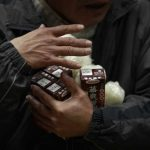 An evacuee collects his food rations in a shelter in Soma city, Fukushima prefecture
