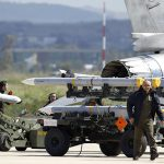 Ground crew transport weapons for an Italian F-16 Fighting Falcon