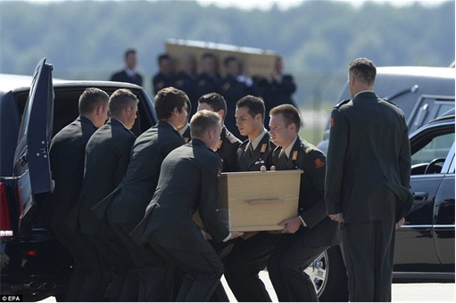 Malaysian Flight MH17 Shot Down - Victims Arrive in Holland - Dutch military personnel putting coffin into hearse