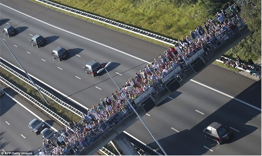 Malaysian Flight MH17 Shot Down - Victims Arrive in Holland - hearses under military police escort - people looking 1
