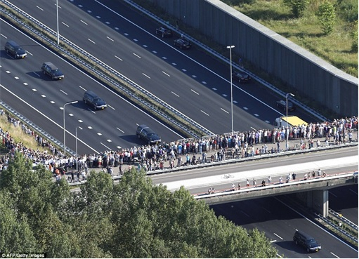 Malaysian Flight MH17 Shot Down - Victims Arrive in Holland - hearses under military police escort - people looking 2