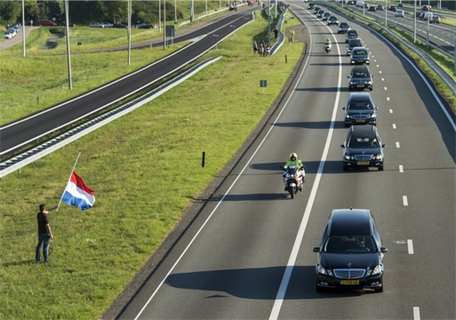 Malaysian Flight MH17 Shot Down - Victims Arrive in Holland - rows of hearses under military police escort - a man carries Dutch flag