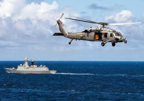 RIMPAC 2014 - An MH-60S Seahawk helicopter, assigned to Helicopter Sea Combat Squadron (HSC) 4, flies over the People's Liberation Army (Navy) frigate Yueyang (FF 575)