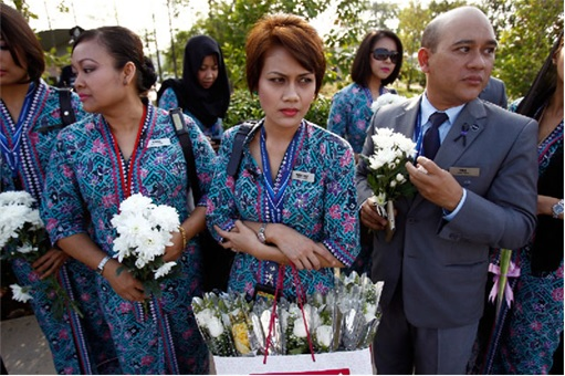 Malaysian Flight MH17 Victims Return Home - MAS staff holding flowers