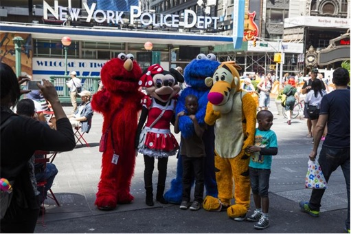 Elmo, Minnie Mouse, Pooh taking photo behind NYPD