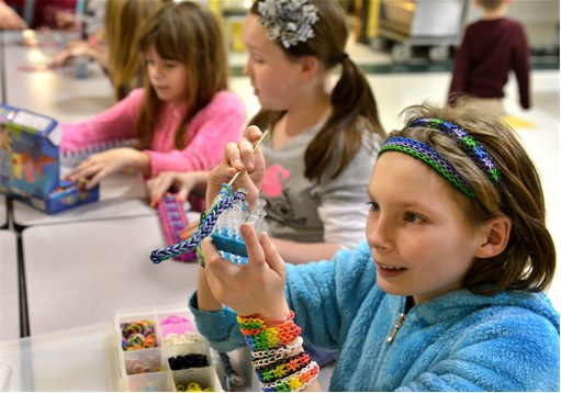 Girls making bracelets using Rainbow Loom