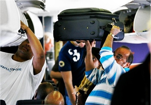 Travellers Cramping Carry-On Luggage Into Compartment