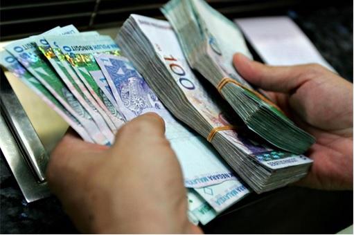 Holding Stacks of Malaysian Ringgit