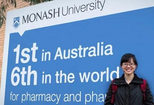 monash-university-student-standing-in-front-of-signboard