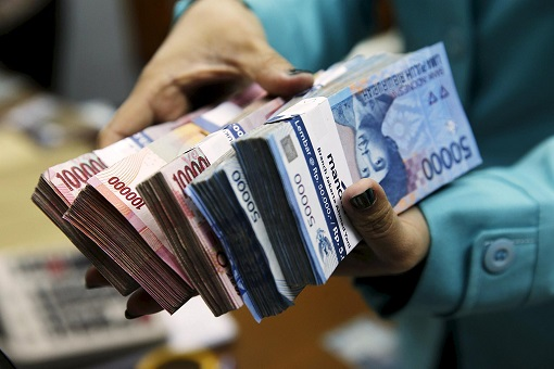 indonesian-currency-holding-stacks-of-rupiah-notes