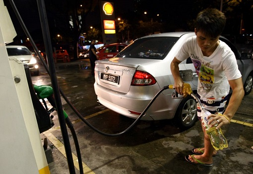 Malaysian Motorist Throng to Fuel Stations - Filling Bottle