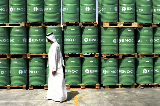 Saudi Walking Passing Barrels of Oil
