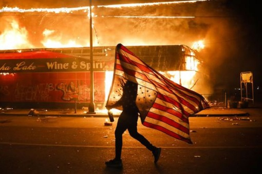 US Race Riots - Carrying American Flag While Buildings Burning