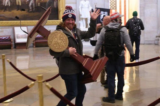 US Capitol Riot Photo - A Smiling Man Carrying Lectern Away