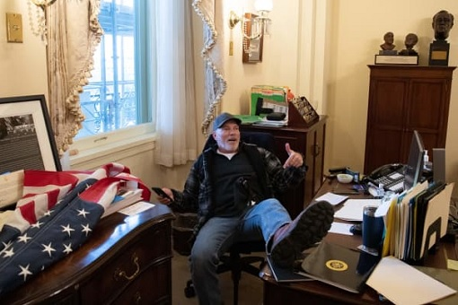 US Capitol Riot Photo - A Trump Supporter Sits Inside the Office of House Speaker Nancy Pelosi