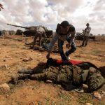 Don't waste - A rebel emptied the pockets of a dead African soldier who had been fighting with Qaddafi's forces